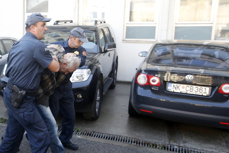 FILE - In this Sunday Oct. 16, 2016 file photo, Montenegrin police officers escort a man suspected of planning armed attacks after the parliamentary vote in Podgorica, Montenegro. (AP Photo/Darko Vojinovic, File)