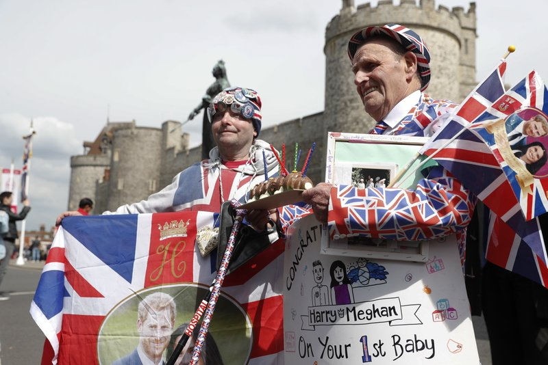 Royal fans John Loughery, left and Terry Hutt pose with flags and banners, outside Windsor Castle, in Windsor, south England, Tuesday, May 7, 2019, a day after Prince Harry announced that his wife Meghan, Duchess of Sussex, had given birth to a boy. (AP Photo/Alastair Grant)