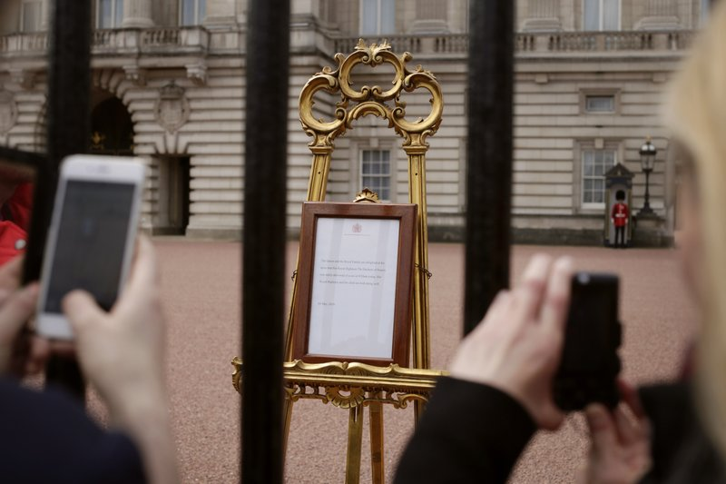 People take pictures of the notice on an easel in the forecourt of Buckingham Palace, London, Tuesday, May 7, 2019, placed on Monday to formally announce the birth of a baby boy to Britain's Prince Harry and Meghan, Duchess of Sussex. (AP Photo/Tim Ireland)