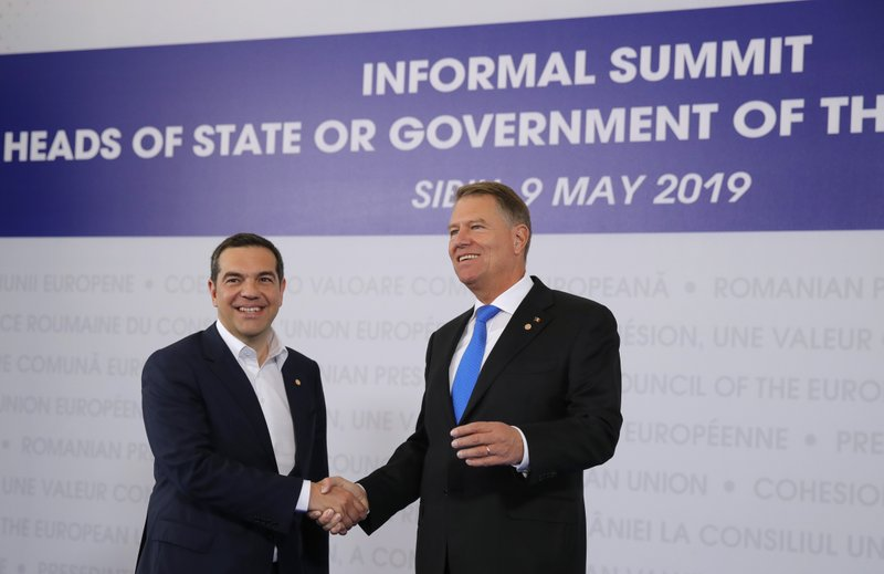 Greek Prime Minister Alexis Tsipras, left, is welcomed by Romanian President Klaus Werner Ioannis as he arrives for an EU summit in Sibiu, Romania, Thursday, May 9, 2019. (AP Photo/Vadim Ghirda)