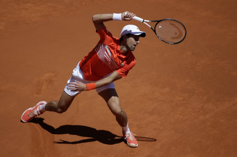 Novak Djokovic, of Serbia, looks at the ball during his match against Jeremy Barty, of France, during the Madrid Open tennis tournament, in Madrid, Spain, Thursday, May 9, 2019. (AP Photo/Andrea Comas)
