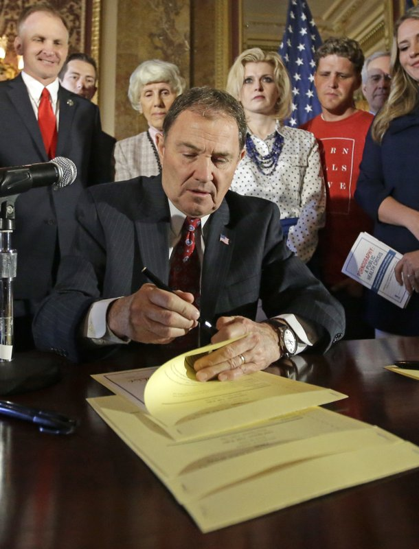 FILE - In this April 19, 2016, file photo, Utah Gov. Gary Herbert looks up during a ceremonial signing of a state resolution declaring pornography a public health crisis, at the Utah State Capitol, in Salt Lake City. (AP Photo/Rick Bowmer, File)