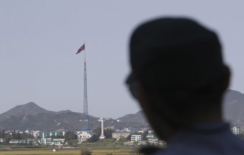 FILE - In this Sept. 28, 2017 file photo, A North Korean flag flutters in the wind atop a 160-meter (525-foot) tower in the North's Kijong-dong village as a South Korean soldier stands near the truce village of Panmunjom in the Demilitarized Zone which has separated the two Koreas since the Korean War, in Paju, South Korea. (AP Photo/Lee Jin-man, File)