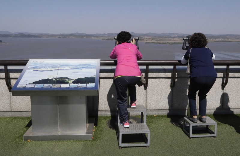 In this May 6, 2019 photo, a visitor uses binoculars to see the North Korea side from the unification observatory in Paju, South Korea. (AP Photo/Lee Jin-man)
