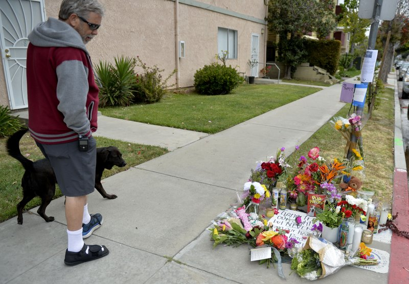 In this Wednesday, May 8, 2019, photo a man and his dog stop at the memorial for Jessica Bingaman, a popular dog walker, who was killed along with five of six dogs she was transporting in Long Beach, Calif. (Brittany Murray/The Orange County Register via AP)
