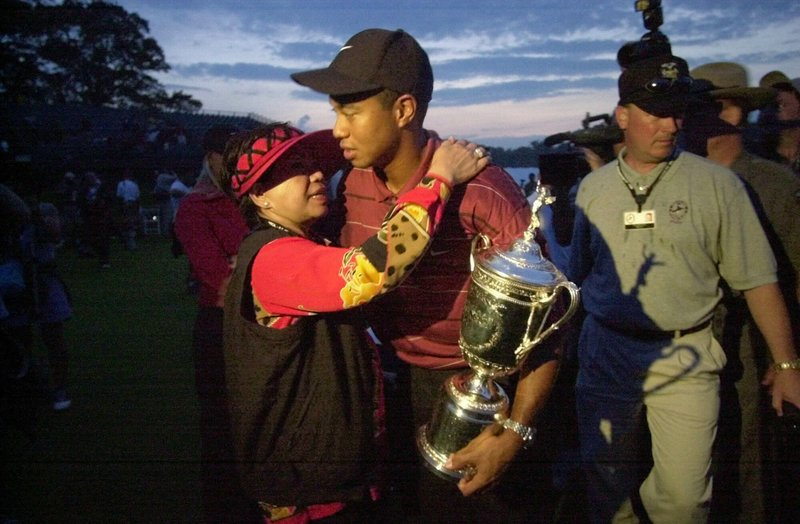 FILE - In this Sunday, June 16, 2002, file photo, Tiger Woods holds his trophy and embraces his mother, Kultida Woods, after winning the U. (AP Photo/Mark Lennihan, File)