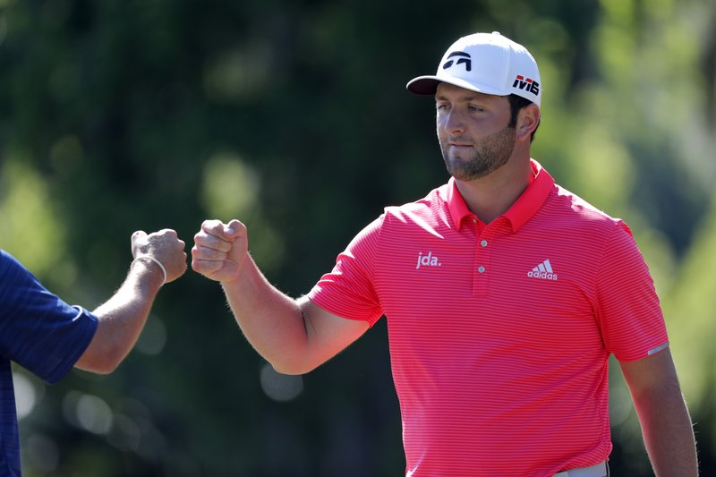 FILE - In this Sunday, April 28, 2019, file photo, Jon Rahm, right, celebrates with teammate Ryan Palmer offer squeaking out a par on the 15th green during the final round of the PGA Zurich Classic golf tournament at TPC Louisiana in Avondale, La. (AP Photo/Gerald Herbert, File)