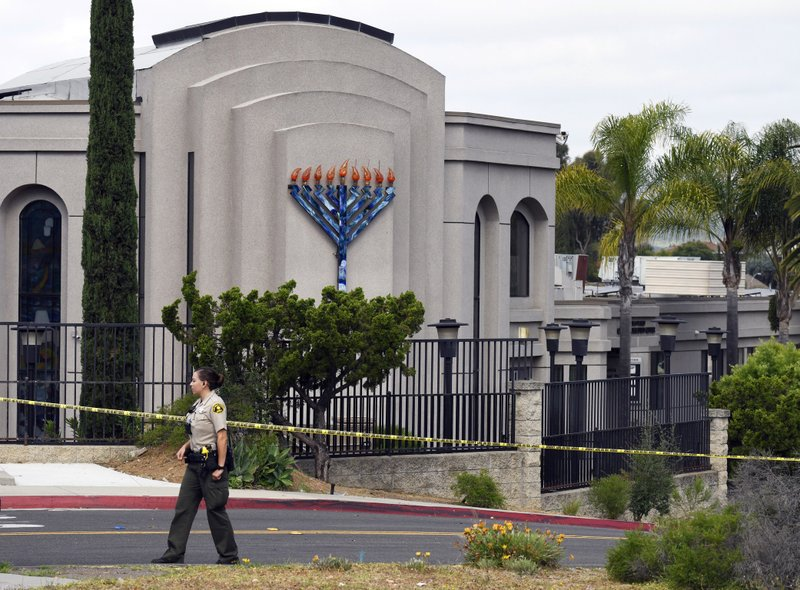 FILE - In this April 28, 2019 file photo, a San Diego county sheriff's deputy stands in front of the Poway Chabad Synagogue in Poway, Calif. (AP Photo/Denis Poroy, File)