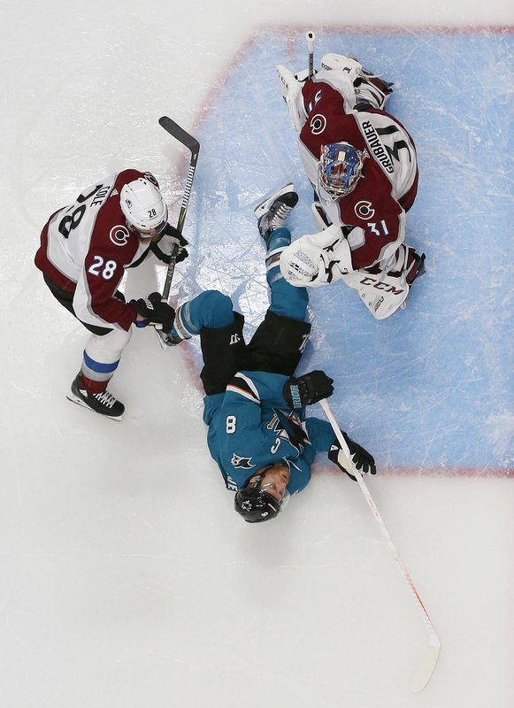 San Jose Sharks center Joe Pavelski (8) falls between Colorado Avalanche defenseman Ian Cole (28) and goaltender Philipp Grubauer (31) during the first period of Game 7 of an NHL hockey second-round playoff series in San Jose, Calif. (AP Photo/Josie Lepe)