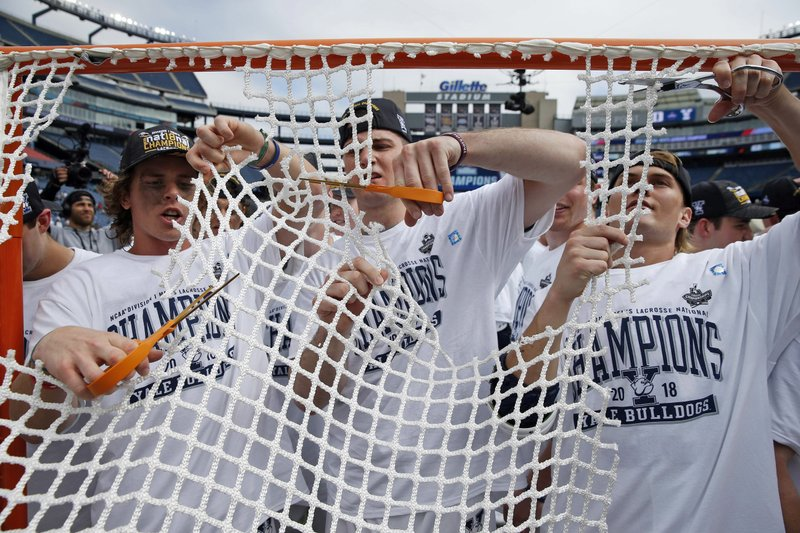 FILE - In this May 28, 2018, file photo, Yale players cut the net after defeating Duke in the championship game of the NCAA college Division I lacrosse tournament in Foxborough, Mass. (AP Photo/Michael Dwyer, File)