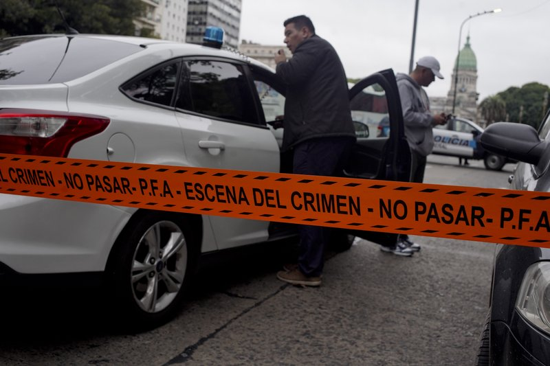 CORRECTS TO CHANGE FROM MOVING VEHICLE TO PARKED CAR - Police stand near the crime scene where Argentine lawmaker Hector Olivares was seriously injured and another man killed after they were shot at from a Parked car near the congressional building, in Buenos Aires, Argentina, Thursday, May 9, 2019. (AP Photo/Natacha Pisarenko)