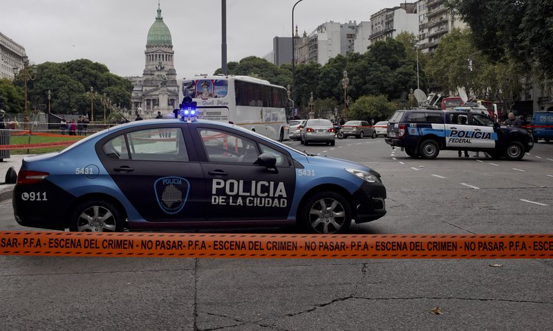 CORRECTS TO CHANGE FROM MOVING VEHICLE TO PARKED CAR - Police cars are parked at the crime scene where Argentine lawmaker Hector Olivares was seriously injured and another man was killed after they were shot at from a parked car near the Congress building, green dome building pictured in background, in Buenos Aires, Argentina, Thursday, May 9, 2019. (AP Photo/Natacha Pisarenko)