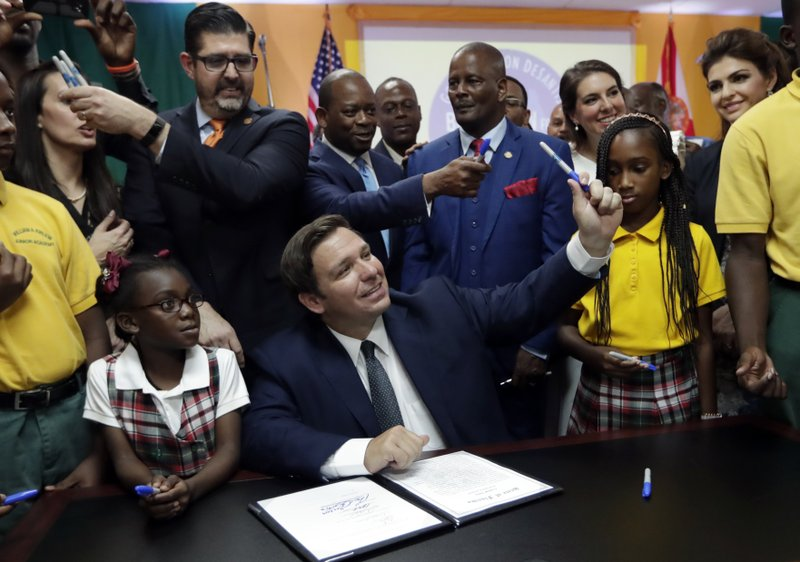 Florida Gov. Ron DeSantis, center, passes out pens used to sign a bill during a signing ceremony at the William J. (AP Photo/Lynne Sladky)