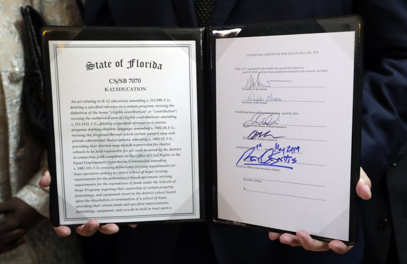 Florida Gov. Ron DeSantis holds a signed bill during a signing ceremony at the William J. Kirlew Junior Academy, Thursday, May 9, 2019, in Miami Gardens, Fla. (AP Photo/Lynne Sladky)