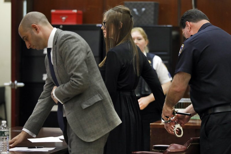 Anna Sorokin has her handcuffs removed as she arrives for sentencing at New York State Supreme Court, in New York, Thursday, May 9, 2019. (AP Photo/Richard Drew)