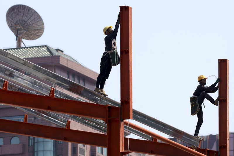 Workers labor in downtown Beijing on Thursday, May 9, 2019. The U.S. effort to win concessions from China on strategic industrial policies has put the Chinese President Xi Jinping's own prestige on the line. (AP Photo/Ng Han Guan)