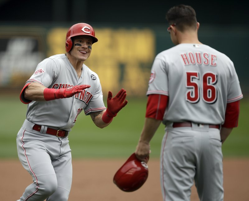 Cincinnati Red's Derek Dietrich, left, celebrates with third base coach J.R. House (56) after hitting a two-run home run off Oakland Athletics' Chris Bassitt in the first inning of a baseball game Thursday, May 9, 2019, in Oakland, Calif. (AP Photo/Ben Margot)