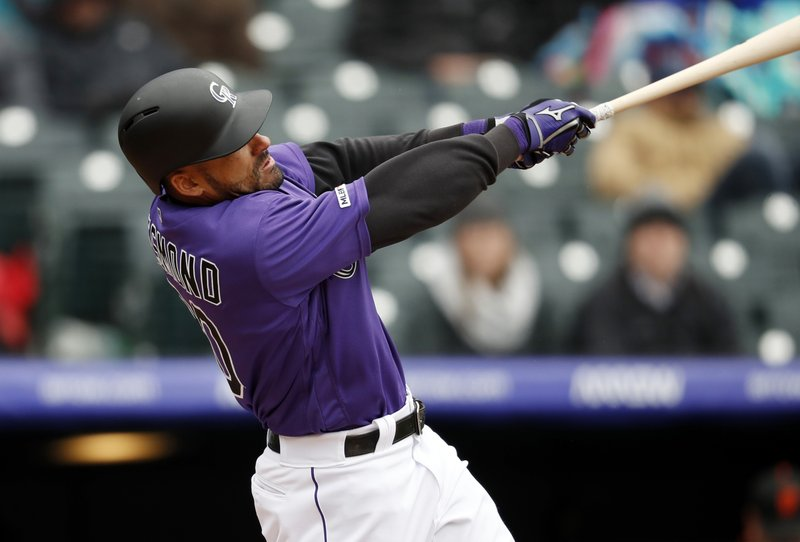 Colorado Rockies' Ian Desmond hits a two-run home run of San Francisco Giants starting pitcher Derek Holland in the second inning of a baseball game Thursday, May 9, 2019, in Denver. (AP Photo/David Zalubowski)