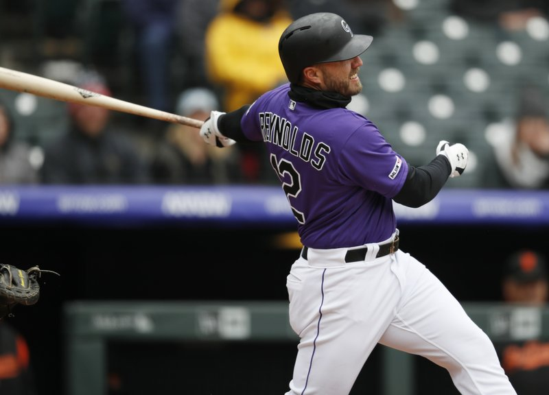 Colorado Rockies' Mark Reynolds follows the flight of his double to drive in two runs off San Francisco Giants starting pitcher Derek Holland in the second inning of a baseball game Thursday, May 9, 2019, in Denver. (AP Photo/David Zalubowski)
