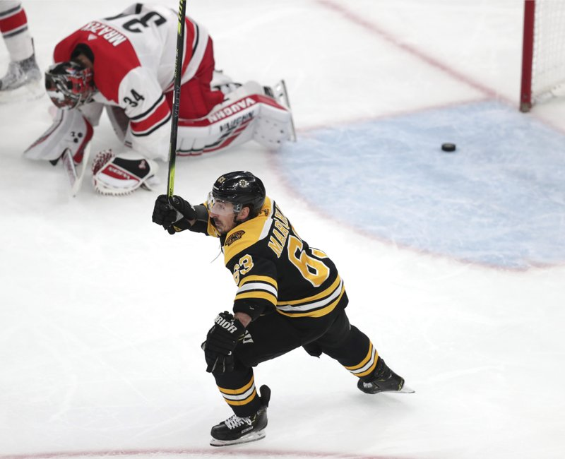 Boston Bruins' Brad Marchand (63) raises his stick as Carolina Hurricanes goaltender Petr Mrazek (34), of the Czech Republic, drops to the ice after a goal by Patrice Bergeron during the third period in Game 1 of the NHL hockey Stanley Cup Eastern Conference finals Thursday, May 9, 2019, in Boston. (AP Photo/Charles Krupa)