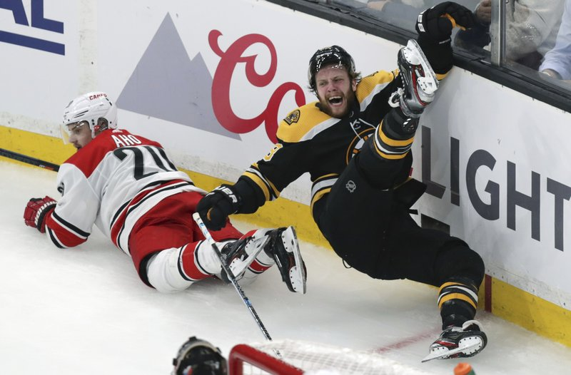 Boston Bruins' David Pastrnak, right, is upended after a check by Carolina Hurricanes' Sebastian Aho (20), of Finland, during the third period in Game 1 of the NHL hockey Stanley Cup Eastern Conference finals Thursday, May 9, 2019, in Boston. (AP Photo/Charles Krupa)