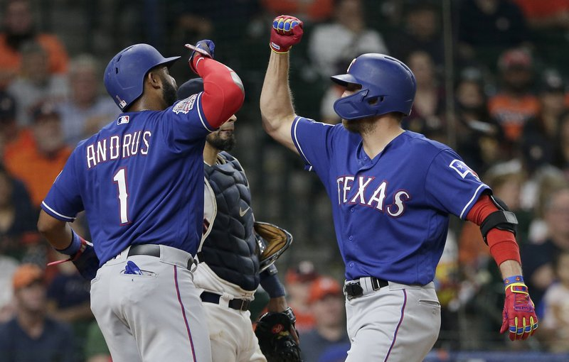 Texas Rangers Elvis Andrus (1) and designated hitter Hunter Pence, right, celebrate at the plate after Pence's two-run home run against the Houston Astros during the fourth inning of a baseball game Thursday, May 9, 2019, in Houston. (AP Photo/Michael Wyke)