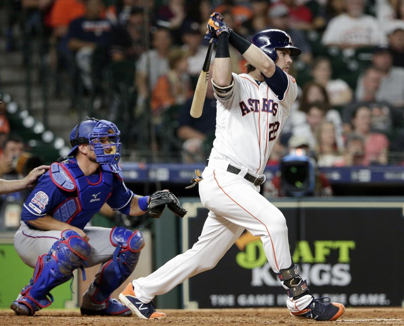 Houston Astros Josh Reddick watches his RBI single in front of Texas Rangers catcher Jeff Mathis during the sixth inning of a baseball game Thursday, May 9, 2019, in Houston. (AP Photo/Michael Wyke)