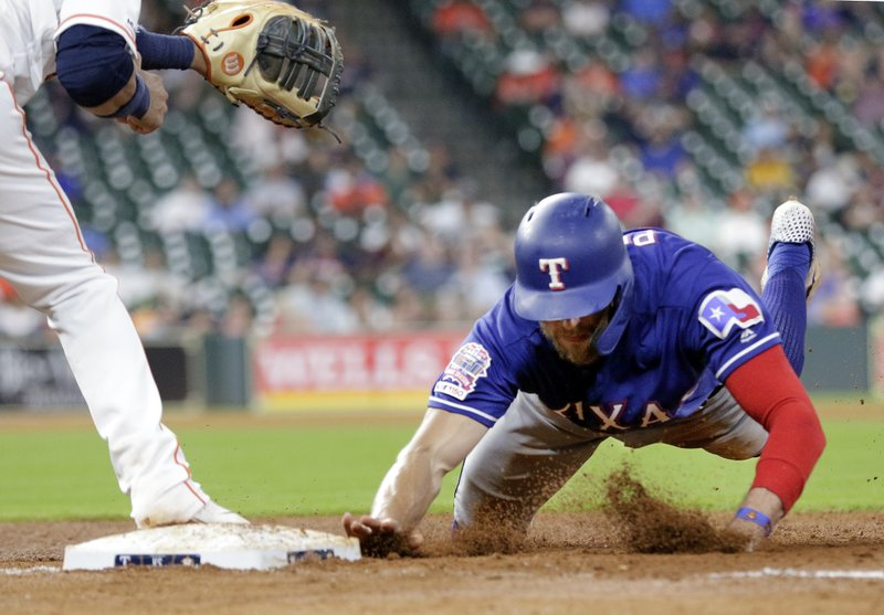 Texas Rangers designated hitter Hunter Pence returns to first as Houston Astros first baseman Yuli Gurriel, left, waits for the throw during the seventh inning of a baseball game Thursday, May 9, 2019, in Houston. (AP Photo/Michael Wyke)
