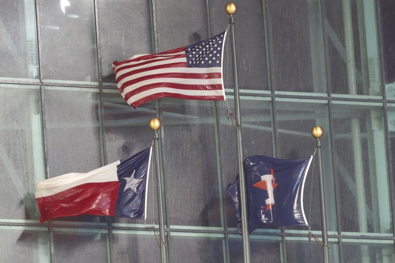 Rain-soaked flags fly under the closed roof as heavy rain leaks into Minute Maid Park during the eighth inning of a baseball game between the Houston Astros and Texas Rangers on Thursday, May 9, 2019, in Houston. (Brett Coomer/Houston Chronicle via AP)