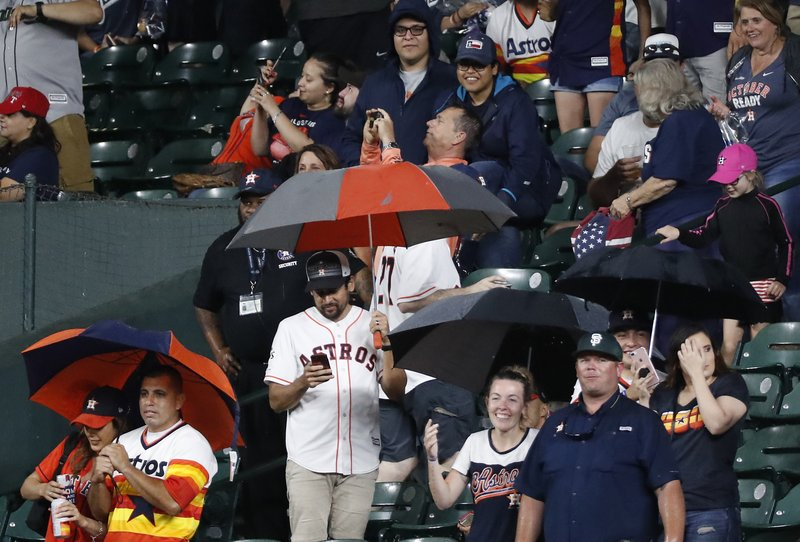 Houston Astros fans take cover under umbrellas as heavy rain leaks into Minute Maid Park during the eighth inning of a baseball game between the Astros and Texas Rangers on Thursday, May 9, 2019, in Houston. (Brett Coomer/Houston Chronicle via AP)