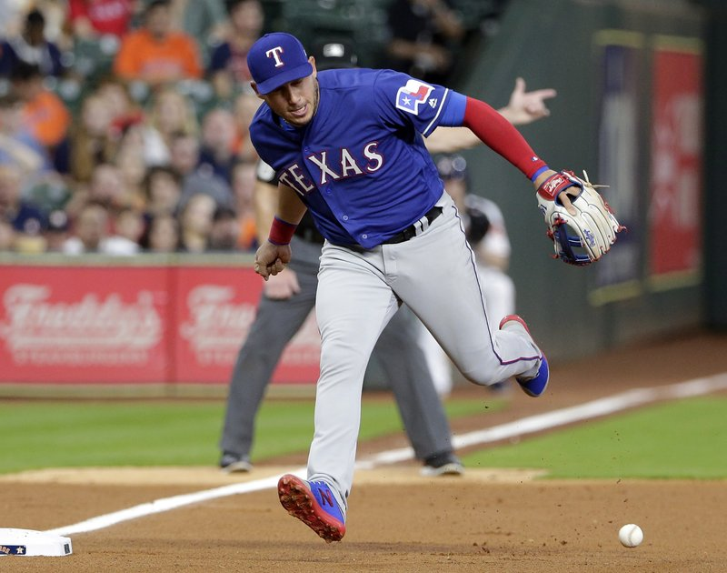 Texas Rangers third baseman Asdrubal Cabrera (14) loses the ball on the infield grounder by Houston Astros George Springer during the first inning of a baseball game Thursday, May 9, 2019, in Houston. (AP Photo/Michael Wyke)