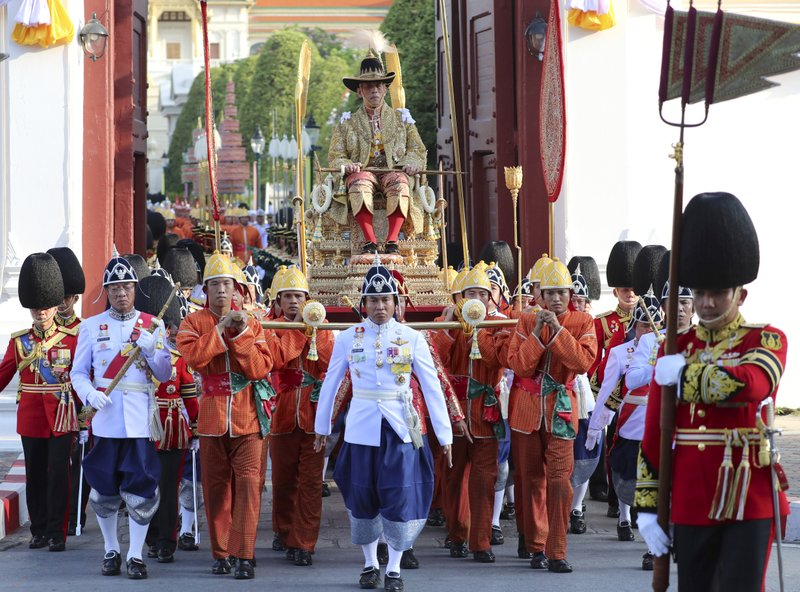 In this May 5, 2019, photo, Thailand's King Maha Vajiralongkorn is transported on the royal palanquin by royal bearers during the Royal Procession on Land to encircle the city for the king's coronation ceremonies in Bangkok, Thailand. (AP Photo/Sakchai Lalit)