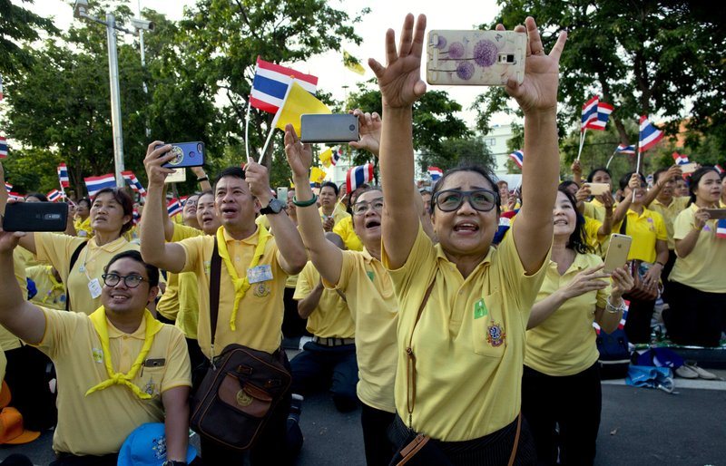 In this May 5, 2019, photo,  people on their knees, reach up to take pictures of King Maha Vajiralongkorn as he passes through the streets during his coronation ceremony in Bangkok, Thailand. (AP Photo/Gemunu Amarasinghe)