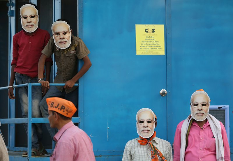 In this May 9, 2019, photo, India's ruling Bharatiya Janata Party (BJP) supporters wear masks of Indian prime minister Narendra Modi and wait for his arrival during an election campaign rally in Prayagraj, India. (AP Photo/Rajesh Kumar Singh)