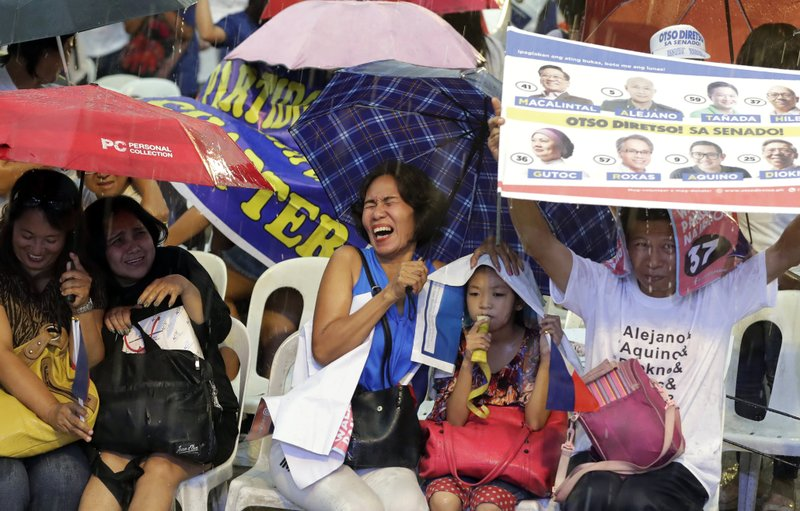 In this May 8, 2019, photo, supporters of the opposition senatorial candidates brave the rain as they listen to speeches at their last campaign rally together, a few days before the May 13 midterm elections in Manila, Philippines. (AP Photo/Bullit Marquez)