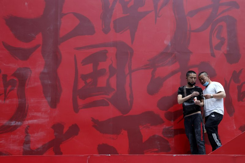 In this May 8, 2019, photo, workers share cigarettes near a booth promoting Made in China with Chinese calligraphy for