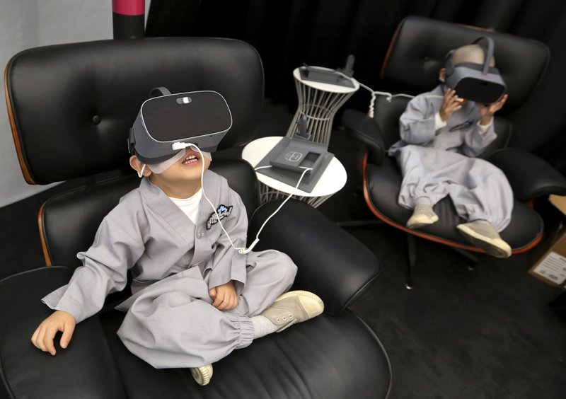 In this May 7, 2019, photo, shaven-headed young boys wear VR devices to experience 5G service at LG UPlus 5G experience place in Seoul, South Korea. (AP Photo/Ahn Young-joon)