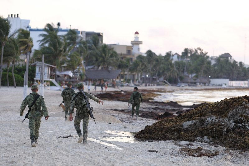 Soldiers walk the beach covered with sargassum seaweed in Playa del Carmen, Mexico, Wednesday, May 8, 2019. (AP Photo/Victor Ruiz)