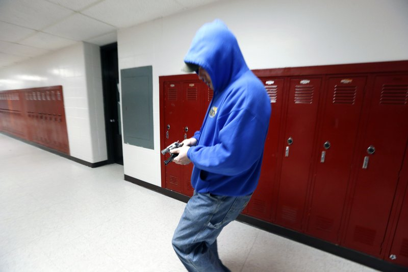 FILE - In this March 15, 2013, file photo, police detective Eric Copeland reloads a pistol with blanks while playing the part of a shooter during a lockdown exercise at Milford High School in Milford, Mass. (AP Photo/Michael Dwyer, File)