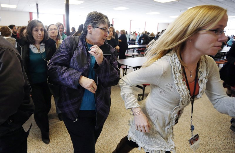 FILE - In this March 15, 2013, file photo, participants rush out of the cafeteria after hearing gun shots during a lockdown exercise at Milford High School in Milford, Mass. (AP Photo/Michael Dwyer, File)