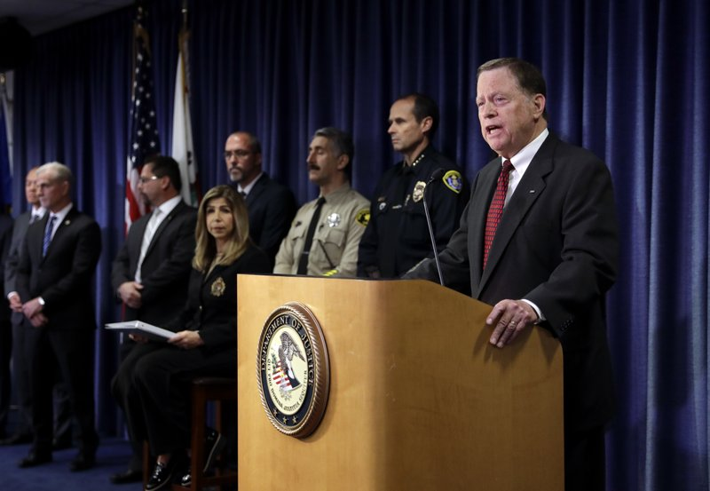 United States attorney Robert S. Brewer, right, speaks during a news conference Thursday, May 9, 2019, in San Diego. (AP Photo/Gregory Bull)