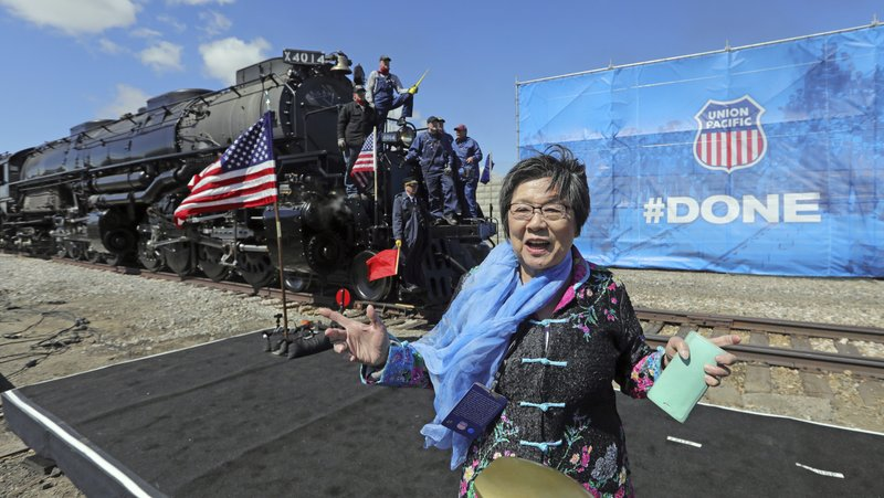 Margaret Yee, whose ancestors helped build the railroad, pose in front of the the Big Boy, No. 4014 during the commemoration of the 150th anniversary of the Transcontinental Railroad completion at Union Station Thursday, May 9, 2019, in Ogden, Utah. (AP Photo/Rick Bowmer)