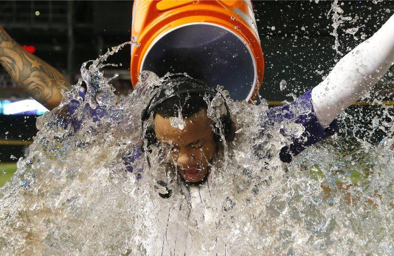 Arizona Diamondbacks' Ketel Marte gets doused with water after his single drove in the winning run in the 10th inning of the team's baseball game against the Atlanta Braves on Thursday, May 9, 2019, in Phoenix. (AP Photo/Ross D. Franklin)