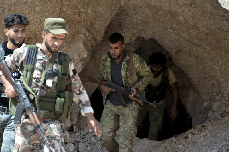 FILE - In this Sept. 9, 2018 file photo, fighters with the Free Syrian army exit a cave where they live, in the outskirts of the northern town of Jisr al-Shughur, Syria, west of the city of Idlib. (Ugur Can/DHA via AP, File)