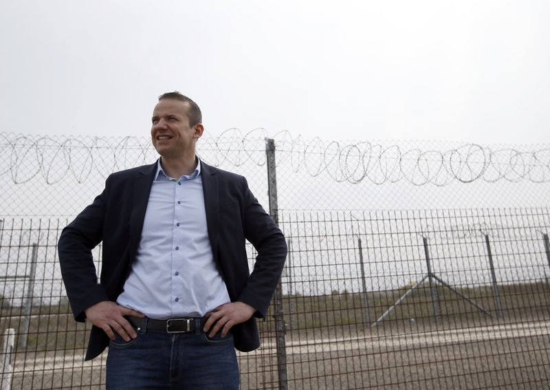 In this photo taken Monday, April 8, 2019, Asotthalom's mayor Laszlo Toroczkai speaks in front of the fence at Hungary's border with Serbia near the village Asotthalom, Hungary. (AP Photo/Darko Vojinovic)