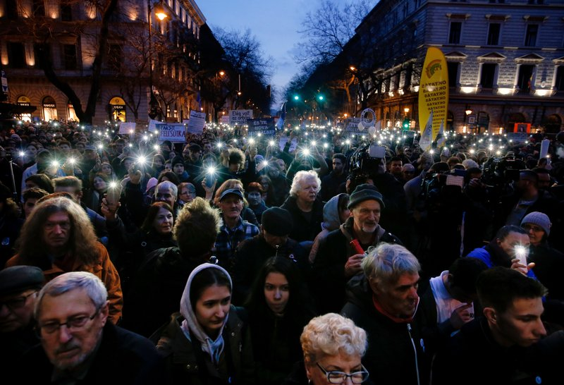 FILE  -  In this Thursday, March 15, 2018, file photo, people taking part in a march against Prime Minister Viktor Orban flash the lights of their mobile phones in Budapest, Hungary. (AP Photo/Darko Vojinovic, File)