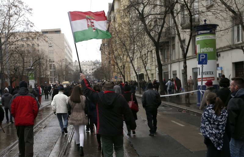 In this March 15, 2018 photo,  a supporter of Hungarian Prime Minister Viktor Orban holds a flag outside the Hungarian Parliament building in Budapest, Hungary, during celebrations of the Hungarian national holiday, the 170th anniversary of the outbreak of the 1848 revolution and war of independence against the Habsburgs. (AP Photo/Darko Vojinovic)
