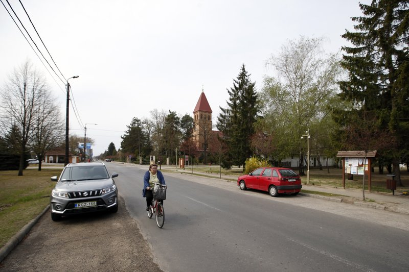 In this photo taken Monday, April 8, 2019, a woman rides a bicycle in the village of Asotthalom, Hungary. (AP Photo/Darko Vojinovic)