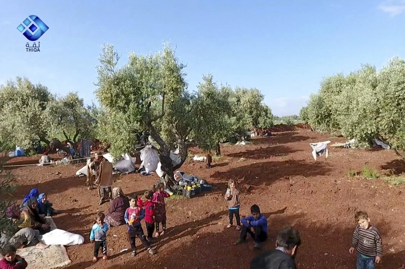 This frame grab from video provided by the activist-operated Thiqa News Agency, shows residents displaced from the latest violence that hit the last rebel stronghold, taking refuge in olives orchids near the town of al-Atmeh, in northern Idlib, Syria, Thursday, May 9, 2019. (Thiqa News Agency via AP)