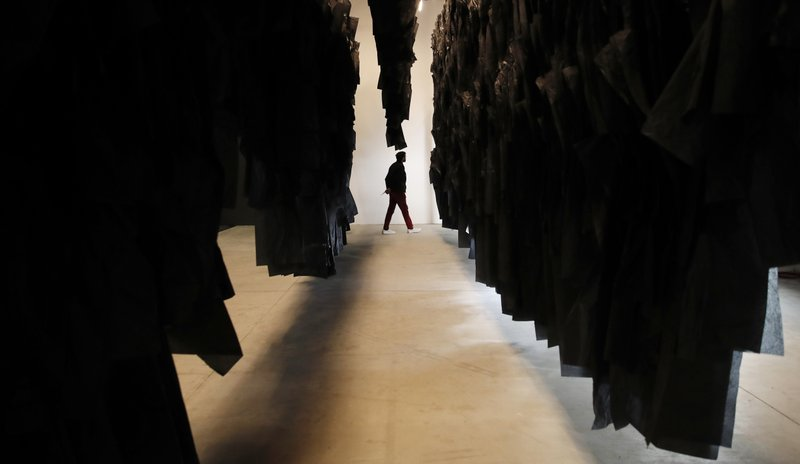 A man walks past an installation at the Madagascar pavilion during the 58th Biennale of Arts exhibition in Venice, Italy, Tuesday, May 7, 2019. (AP Photo/Antonio Calanni)